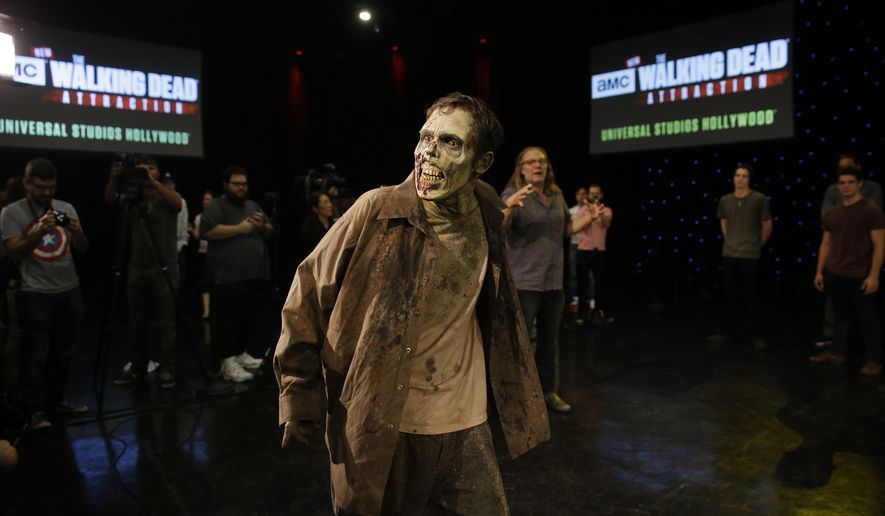 """In this Wednesday, June 8, 2016 photo, Joe Giles, an actor portraying a zombie in """"The Walking Dead,"""" demonstrates how to walk like a zombie during a walker boot camp at Universal Studios Hollywood in Los Angeles. (AP Photo/Jae C. Hong)"""