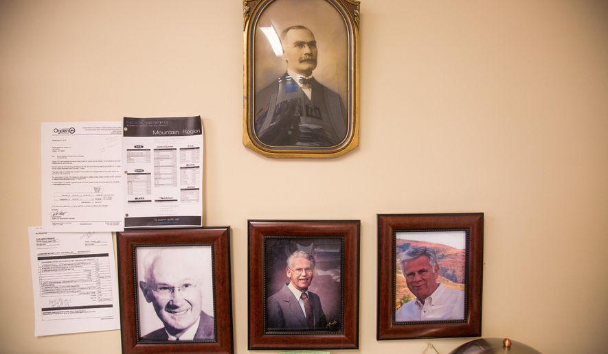 In this Thursday, June 15, 2016 photo, photos of Mclaren, top, Albert, left, Pete, center, and Jim Boyle hang in an office at Boyle Appliance Center in Ogden, Utah. Jim Boyle is the sixth generation to own the family business and is currently in the process of retiring and passing it on to his children. (Benjamin Zack /Standard-Examiner via AP) TV OUT; MANDATORY CREDIT