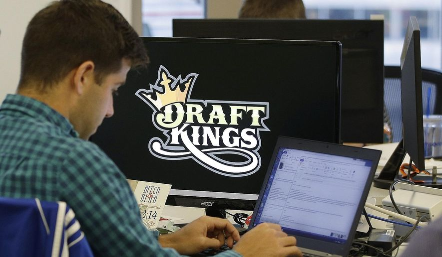 FILE - In this Sept. 9, 2015, file photo, Bear Duker, a marketing manager for strategic partnerships at DraftKings, works at his computer at the company headquarters in Boston. Gambling analysts said the daily fantasy sports company has struggled to break out in the UK since it launched to fanfare there in February 2016. (AP Photo/Stephan Savoia, File)
