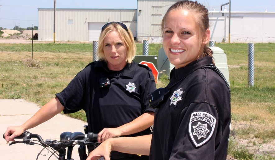 ADVANCE FOR USE SATURDAY, JUNE 25 - In this photo taken June 17, 2016, Hall County Sheriff's Deputies Melissa Kier, left, and Camela Jiskra, the newest members of the department's bicycle partol, pose by their bicycles in Grand Island, Neb. (Jeff Bahr /The Independent via AP) MANDATORY CREDIT