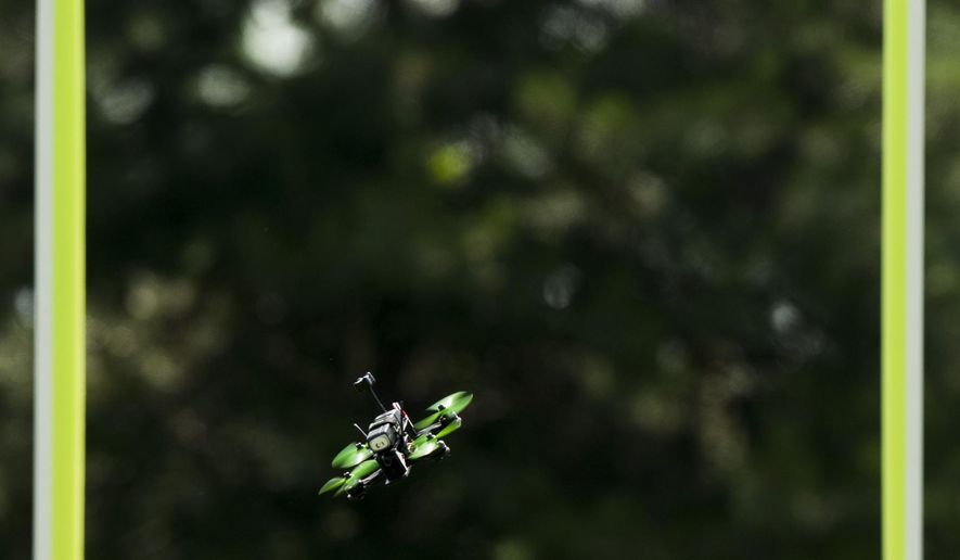 A drone zooms through an obstacle while its operator competes in a drone race conducted by the local Nebraska Drone Racing chapter of MultiGP on  June 18, 2016,  near University of Nebraska-Lincoln East Campus.  Each drone has a small camera attached that relays a signal to a virtual reality headset worn by its pilot, giving the controller the perception of being inside the drone. (Matt Ryerson/The Journal-Star via AP) LOCAL TELEVISION OUT; KOLN-TV OUT; KGIN-TV OUT; KLKN-TV OUT; MANDATORY CREDIT