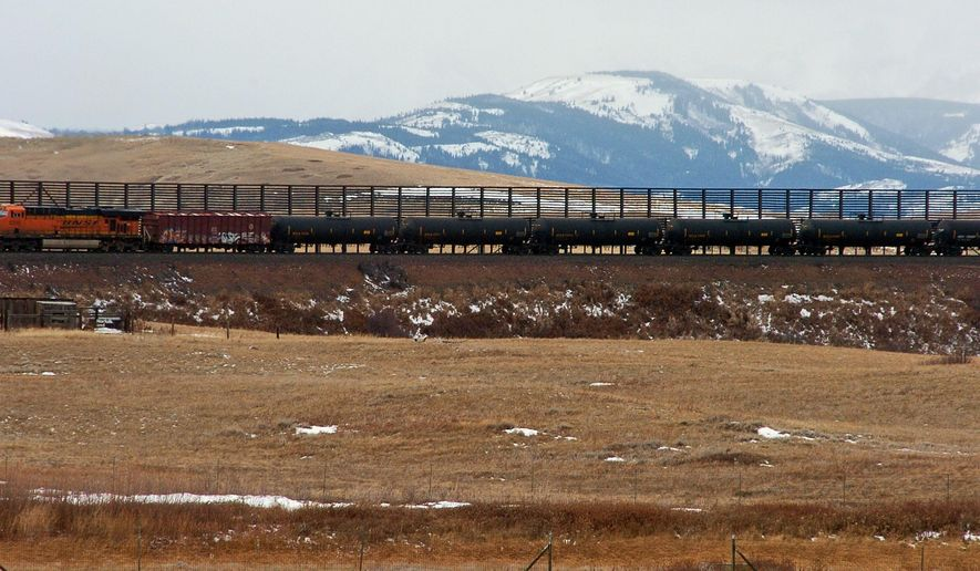 FILE--In this Nov. 7, 2013 file photo, a train hauls oil into Glacier National Park near the Badger-Two Medicine National Forest in northwest Montana. Companies proposing to build the nation's largest oil-by-rail marine terminal in southwest Washington state and their foes will argue their cases before a state energy panel in Vancouver, Wash., on Monday, June 27, 2016. (AP Photo/Matthew Brown, File)
