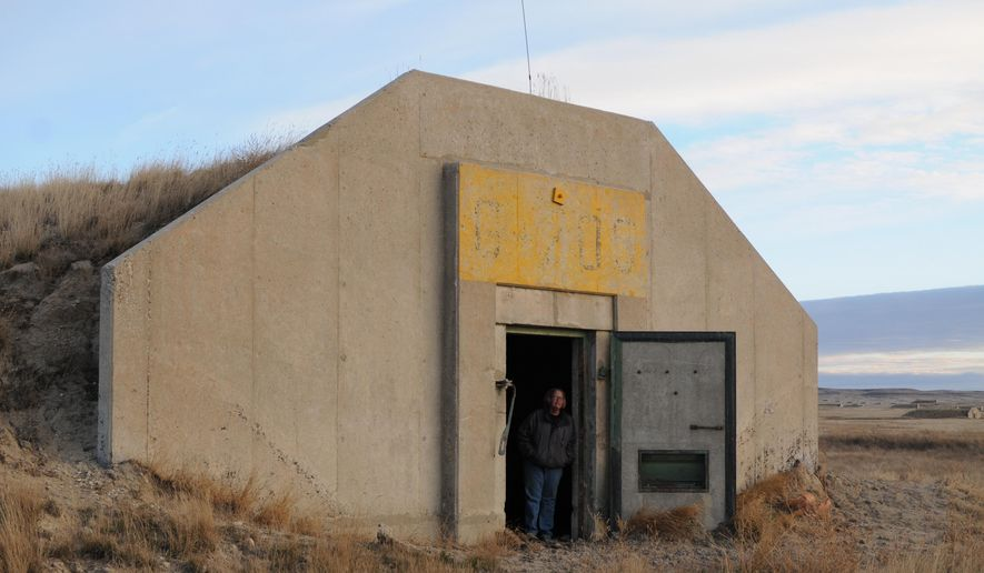 In this Thursday, Nov. 19, 2015, photo Rancher Cindy Brunson stands in the doorway of an earthen igloo-like bunker at the former Black Hills Army Depot in Fall River County, S.D. The U.S. Army Corps of Engineers is installing barbed-wire fence to close off part of the defunct military depot near Edgemont, but some locals say it will be ineffective at stopping potential danger from lingering explosives and contamination.  (AP Photo/James Nord)