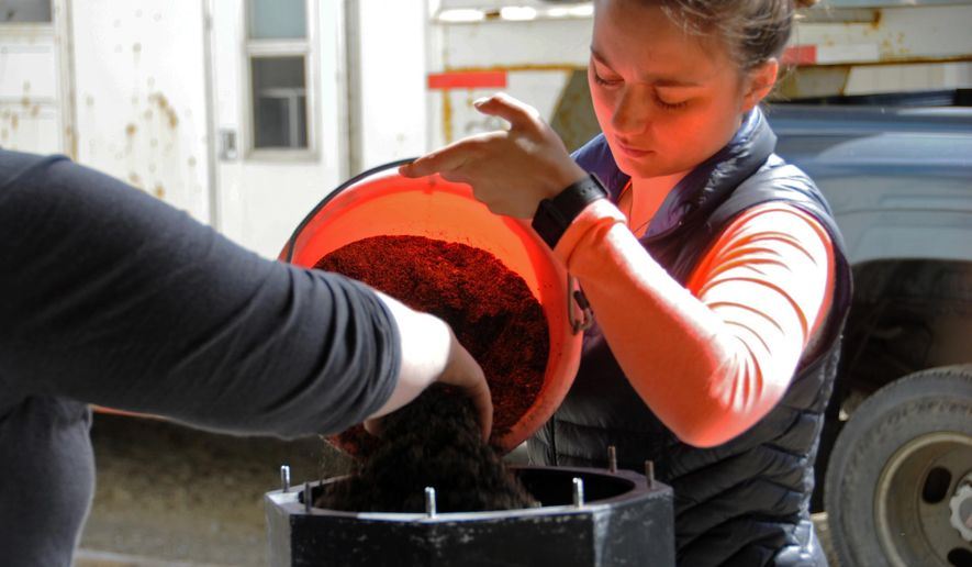In this Wednesday, June 1, 2016 photo, Jenna Hansen and her sister Megan pour grit into the tumbler where their recycled glass will be smoothed at their home in Nikiski, Alaska. Hansen and her family turn recycled glass into handmade jewelry that they sell. (Elizabeth Earl/Peninsula Clarion via AP) MANDATORY CREDIT