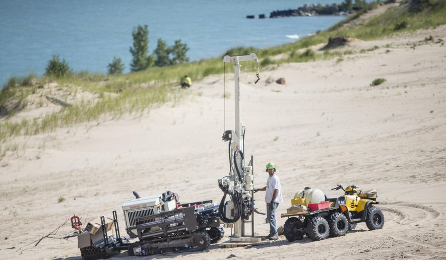 FILE - In this Aug. 14, 2014 file photo, a researcher uses large equipment to study Indiana Dunes National Lakeshore's Mount Baldy in Michigan City, Ind.   Mysterious holes that forced the closure of a massive dune at an Indiana national park after a 6-year-old boy fell into one and nearly died were caused by sand-covered trees that left cavities behind as they decayed over the years, researchers have found.  (Robert Franklin/South Bend Tribune via AP) MANDATORY CREDIT
