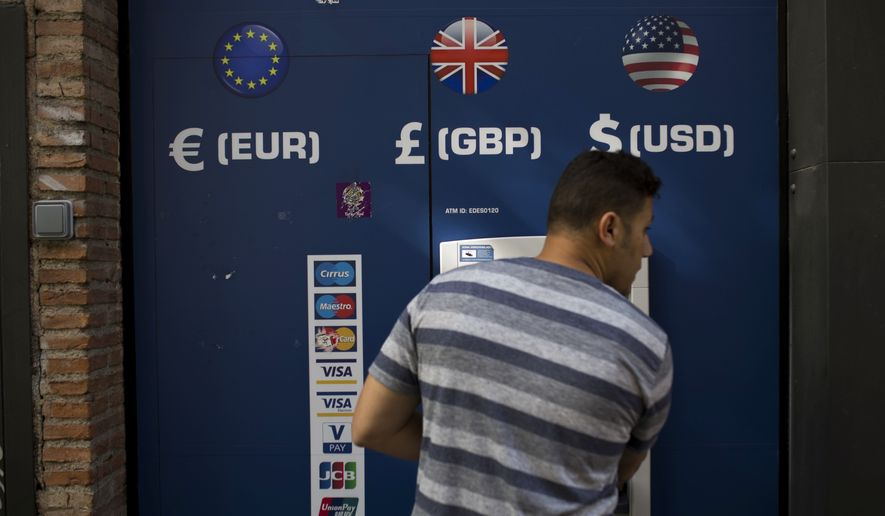A man uses a multi currency ATM in downtown Madrid, Spain. (Associated Press)