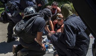 A victim is attended after he was stabbed during a rally Sunday at the State Capitol in Sacramento, Calif., on Sunday. (The Sacramento Bee via Associated Press)