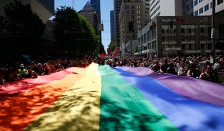 People help carry the rainbow flag during the the 42nd annual Seattle Pride Parade on Sunday, June 26, 2016. (Sophia Nahli Allison/The Seattle Times via AP) MANDATORY CREDIT