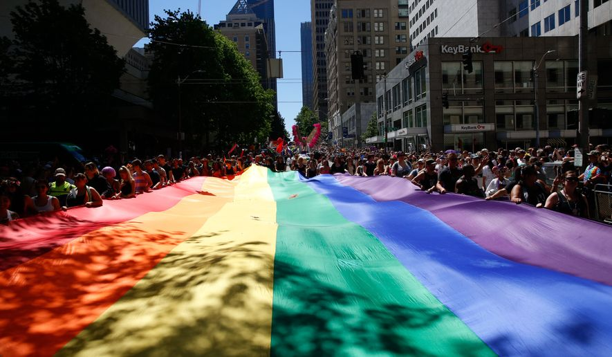 People help carry the rainbow flag during the the 42nd annual Seattle Pride Parade on Sunday, June 26, 2016. (Sophia Nahli Allison/The Seattle Times via AP) ** FILE **