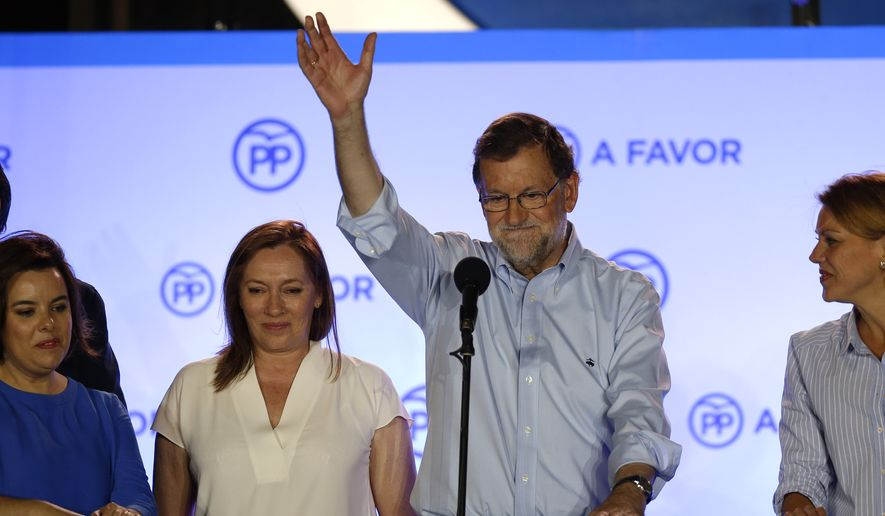 Spain's acting Prime Minister and candidate of Popular Party Mariano Rajoy waves to his supporters next to his party members as they celebrate the results of their party during the national elections in Madrid, Spain, Sunday, June 26, 2016. (AP Photo/Daniel Ochoa de Olza)