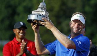 Billy Hurley III, right, acknowledges the gallery in front of Tiger Woods after winning the Quicken Loans National PGA golf tournament, Sunday, June 26, 2016, in Bethesda, Md. (AP Photo/Patrick Semansky)