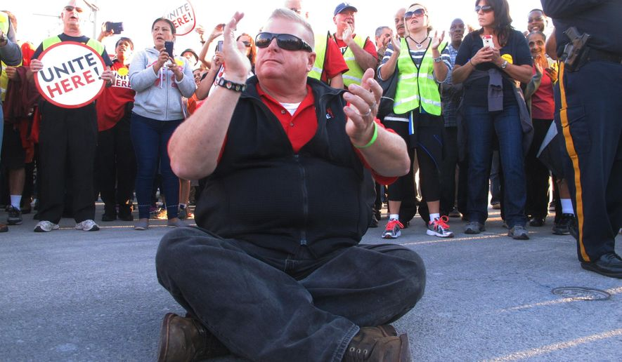 In this Oct. 8, 2014 photo, Bob McDevitt, president of Local 54 of the Unite-HERE casino workers union, sits in the roadway to block traffic on the Atlantic City Expressway in Atlantic City, N.J., during a protest against benefit cuts for workers. On Thursday, June 23, 2016, the union will begin airing radio advertisements outlining why it is threatening to go on strike as of July 1 if a new contract is not reached that restores some of what union members gave back to the casinos in past contracts. (AP Photo/Wayne Parry)