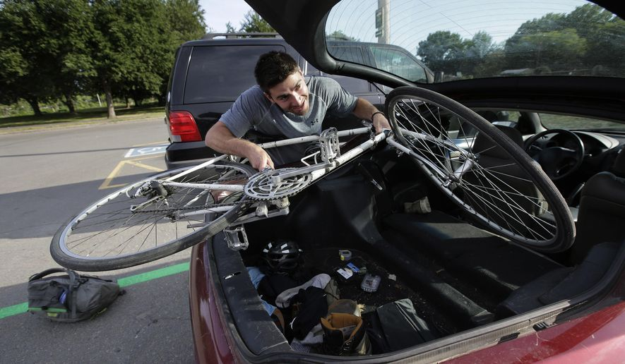 In this Thursday, June 23, 2016 photo William Spiro, of Newton, Mass., removes his bike from his car at a Park & Pedal area in a parking lot, in Boston, as he prepares to complete his morning commute. The recently expanded Park & Pedal program offers motorists a chance to park their cars for free and then bike the rest of the way to work. (AP Photo/Steven Senne)
