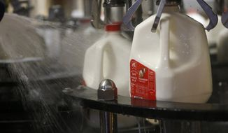 In this Tuesday, June 14, 2016, file photo, bottles of whole milk are rinsed off as they go through the production line at the Anderson Erickson milk plant in Des Moines, Iowa. Two percent and whole milk sales have climbed, while fat-free milk demand has declined. (Michael Zamora/The Des Moines Register via AP)  ** FILE **