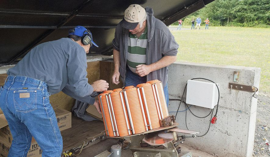 ADVANCE FOR WEEKEND EDITIONS, JUNE 25-26 - In this photo taken Saturday, June 11, 2016, Newberg Rod and Gun Club members Nick Scarla and Rick Grauer reload a trap with clay pigeons during kids' shooting day at the Newberg Rod and Gun Club in Newberg, Ore. The 70-year old organization has shifted toward a more family friendly atmosphere, boosting membership and revenue. (Marcus Larson/News-Register via AP) MANDATORY CREDIT