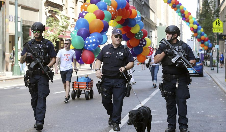Heavily armed police officers walk along the street near the parade route of the New York City Pride Parade on Sunday, June 26, 2016, in New York City. A year after New York City's storied gay pride parade celebrated a high point with the legalization of gay marriage nationwide, the atmosphere this year couldn't be more different. Parades in New York and other major cities Sunday will feature increased security, anti-violence messages and tributes to those killed in this month's massacre at a gay nightclub in Florida. (AP Photo/Mel Evans)