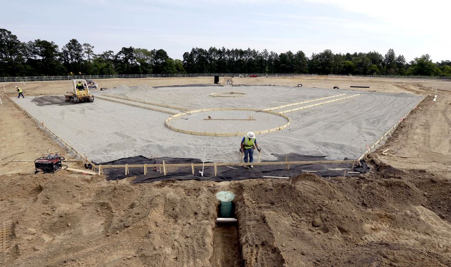 In this photo taken Wednesday, April 20, 2016, contractors install a baseball field at Fort Bragg, N.C. The race is on to build a big-league baseball field from scratch. The Atlanta Braves and Miami Marlins will play a salute-the-troops game at this vast U.S. Army post the night before Independence Day. (AP Photo/Gerry Broome)