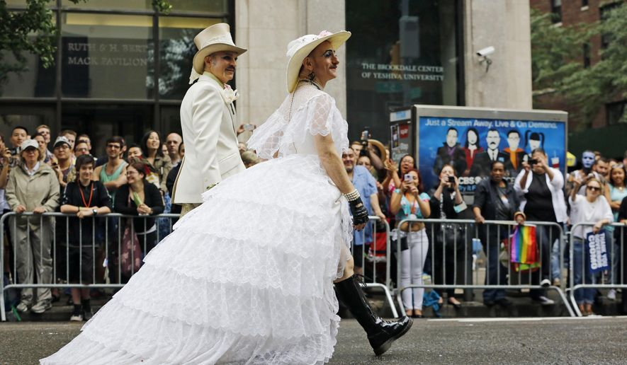 FILE - In this June 28, 2015 file photo, Scott Parent, left, and Tigger! Ferguson, wearing a wedding dress, parade down Fifth Avenue during the Heritage Pride March in New York where to mood was festive following the landmark Supreme Court ruling that said gay couples can marry anywhere in the country. The atmosphere this year couldn't be more different. Parades in New York and other major cities Sunday will feature increased security, anti-violence messages and tributes to those killed in this month's massacre at a gay nightclub in Florida. (AP Photo/Kathy Willens, File)