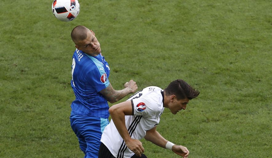 Slovakia's Martin Skrtel, left, and Germany's Mario Gomez challenge for the ball during the Euro 2016 round of 16 soccer match between Germany and Slovakia, at the Pierre Mauroy stadium in Villeneuve d'Ascq, near Lille, France, Sunday, June 26, 2016. (AP Photo/Darko Vojinovic)