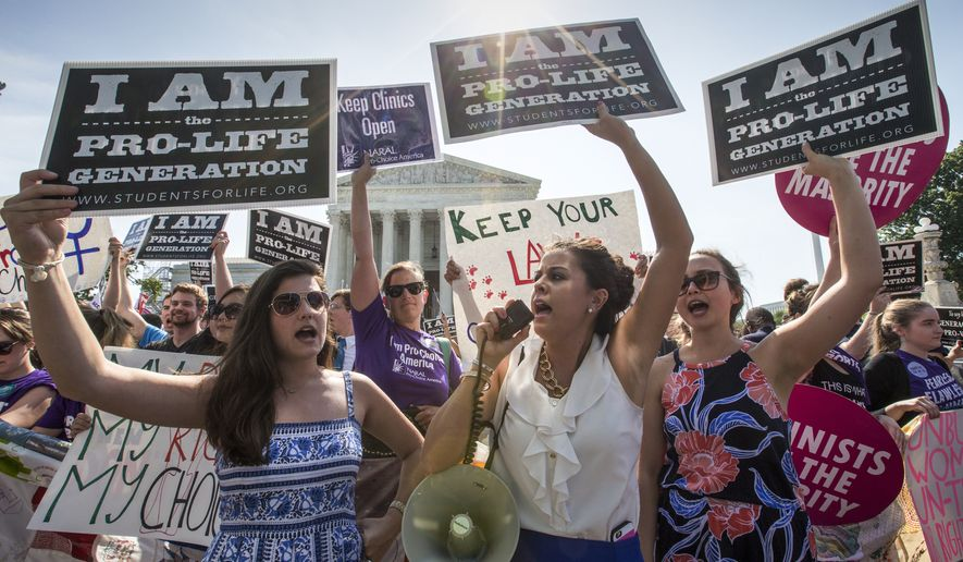 In this file photo, Reagan Barklage of St. Louis, center, and other pro-life activists demonstrate in front of the U.S. Supreme Court in Washington, Monday, June 27, 2016, when the justices struck down the strict Texas anti-abortion restriction law known as HB2. (AP Photo/J. Scott Applewhite) **FILE**