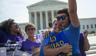 Bethany Van Kampen, left, hugs Alejandra Pablus as they celebrate during a rally at the Supreme Court in Washington, Monday, June 27, 2016, after the court struck down Texas' widely replicated regulation of abortion clinics. The justices voted 5-3 in favor of Texas clinics that had argued the regulations were a thinly veiled attempt to make it harder for women to get an abortion in the nation's second-most populous state. (AP Photo/Evan Vucci)