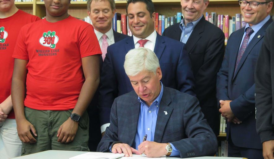 Gov. Rick Snyder is joined by lawmakers and students as he signs a $16.1 billion education budget bill, Monday, June 27, 2016, at the James R. Geisler Middle School in Commerce Township, Mich. (AP Photo/David Eggert)