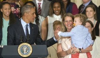 President Barack Obama, left, gets a high five from Oliver, son of Minnesota Lynx head coach Cheryl Reeve, right, in the East Room of the White House in Washington, Monday, June 27, 2016, during a ceremony where he honored the 2015 WNBA basketball Champion Minnesota Lynx. (AP Photo/Pablo Martinez Monsivais)
