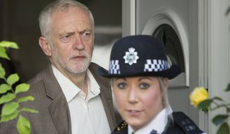 Britain's Labour Party leader Jeremy Corbyn leaves his home escorted by a police-officer to help through the media to a waiting vehicle  in north London Tuesday June 28, 2016. The opposition leader Jeremy Corbyn faced upheaval within his Labour Party after a number of Labour Party lawmakers, called on him to resign following Britain's EU referendum result.  (Rick Findler/PA via AP)