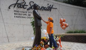 Teresa Olive, of Knoxville, Tenn., touches a statue of Pat Summitt as she pays her respects at the University of Tennessee, on Tuesday, June 28, 2016, in Knoxville, Tenn. Summitt, the winningest coach in Division I college basketball history who uplifted the women's game from obscurity to national prominence during her career at Tennessee, died Tuesday morning, June 28, 2016. She was 64. (Caithe McMekin/Knoxville News Sentinel via AP) MANDATORY CREDIT