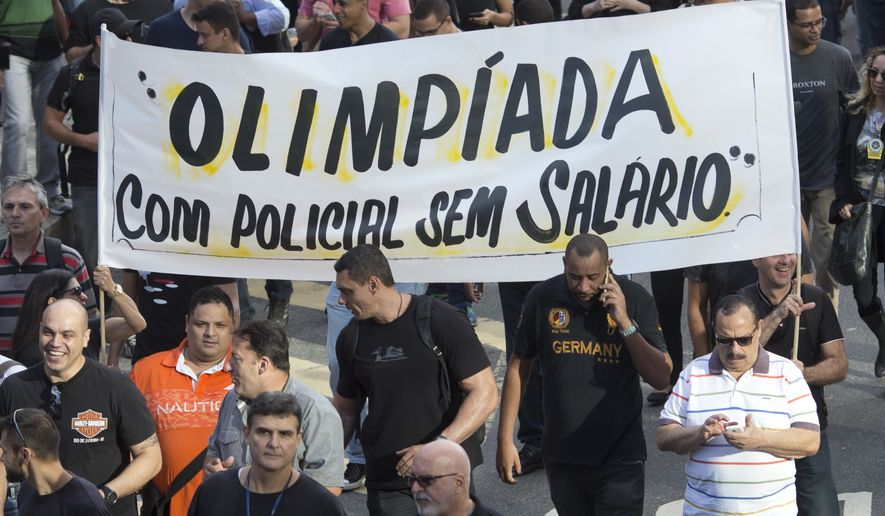 "Civil police officers protest with a banner that reads in Portuguese ""Olympics with unpaid police"" in Rio de Janeiro, Brazil, Monday, June 27, 2016. Just weeks ahead of the Olympic Games, police helicopters are grounded, patrol cars are parked and Rio de Janeiros security forces are so pressed for funds that some have to beg for donations of pens, cleaning supplies and even toilet paper, fueling worries about safety at the worlds premier sporting event. (AP Photo/Silvia Izquierdo)"