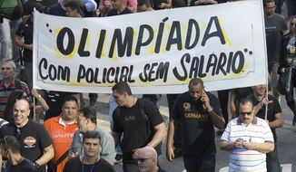"""Civil police officers protest with a banner that reads in Portuguese """"Olympics with unpaid police"""" in Rio de Janeiro, Brazil, Monday, June 27, 2016. Just weeks ahead of the Olympic Games, police helicopters are grounded, patrol cars are parked and Rio de Janeiros security forces are so pressed for funds that some have to beg for donations of pens, cleaning supplies and even toilet paper, fueling worries about safety at the worlds premier sporting event. (AP Photo/Silvia Izquierdo)"""