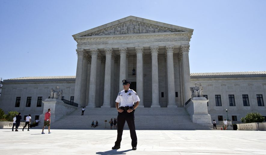 FILE - In this June 20, 2016 file photo, a Supreme Court police officer stands in front of the Supreme Court in Washington as the court announced several decisions.  Justice Antonin Scalias sudden death transformed the Supreme Courts term, shifted power to its liberal wing and started a transition that will be greatly affected by who wins the presidency. It was a term unusual in other ways, too. Justice Clarence Thomas broke a 10-year silence following his good friends death to ask questions during an oral argument. Senate Republicans shunned any action on President Barack Obamas nominee to restore the court to its full nine-member strength. And four cases ended in 4-4 ties. (AP Photo/Alex Brandon, File)