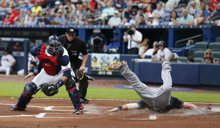 Cleveland Indians' Jason Kipnis (22) scores ahead of the throw to Atlanta Braves catcher A.J. Pierzynski (15) on a Jose Ramirez base hit in the first inning of a baseball game Tuesday, June 28, 2016, in Atlanta. (AP Photo/John Bazemore)