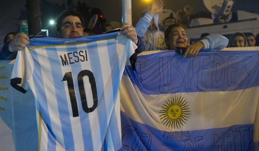 A fans holds an national soccer team jersey with the name and number of Lionel Messi as the bus with the national team arrives to the Argentina Soccer Association, Monday, June 27, 2016, in Buenos Aires, Argentina. Lionel Messi says he's quitting Argentina's national team after loosing a final for the third year in a row, with Chile winning the Copa America 4-2 on penalty kicks following a 0-0 tie Sunday night. (AP Photo/Natacha Pisarenko)