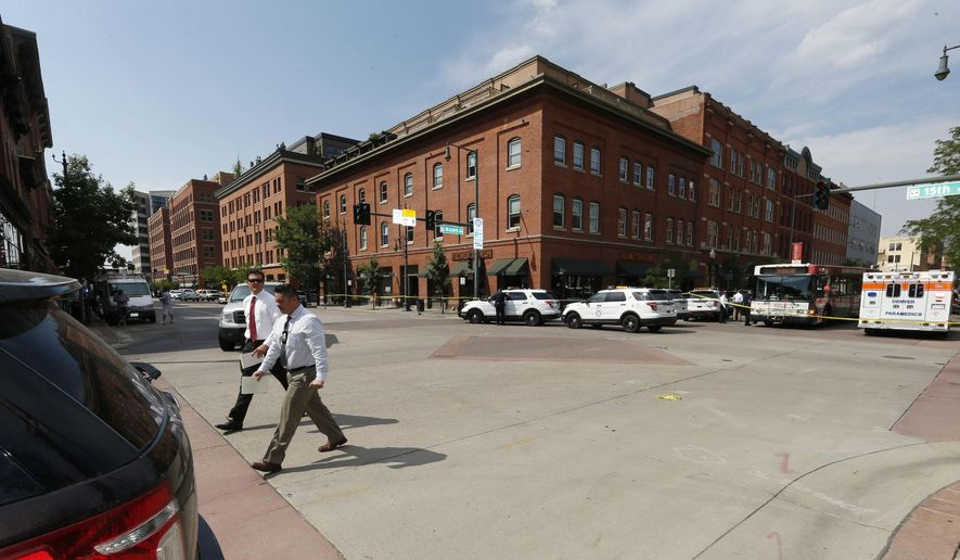 Investigators walk through the intersection of 15th Street and Wazee near the scene of a shooting in a lower downtown business Tuesday, June 28, 2016, in Denver. Officers responded to the business after a report of a gunman, blocking several streets in the congested area. (AP Photo/David Zalubowski)
