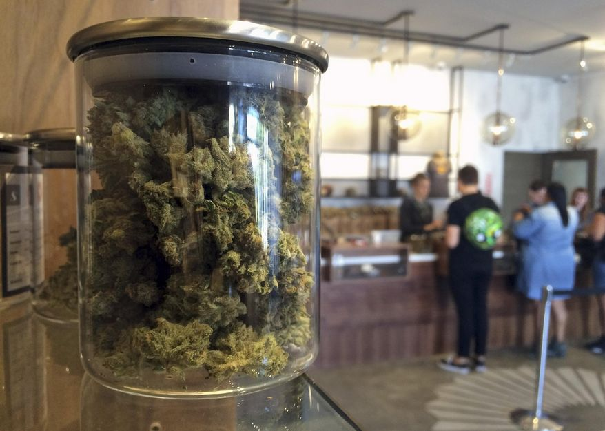 File - In this April 20, 2016 file photo, customers buy products at the Harvest Medical Marijuana Dispensary in San Francisco. (AP Photo/Haven Daley, File)