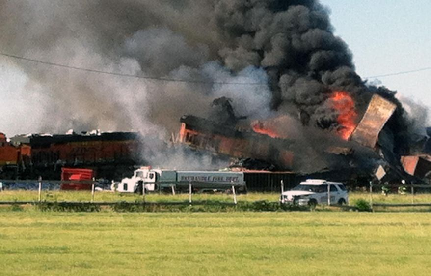 In this photo provided by Billy B. Brown, two freight trains are on fire Tuesday, June 28, 2016, after they collided and derailed near Panhandle, Texas. Texas Department of Public Safety Lt. Bryan Witt says the accident occurred Tuesday morning near the town of Panhandle, about 25 miles northeast of Amarillo. No injuries have been reported. (Billy B. Brown via AP)