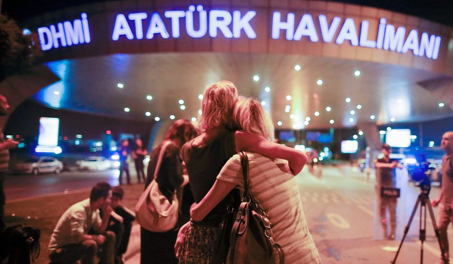 Passengers embrace at the entrance to Istanbul's Ataturk Airport after evacuating during Tuesday's attack. (Associated Press)