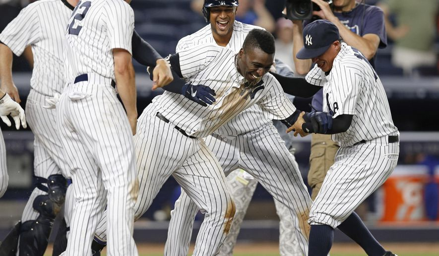 Teammates celebrate with New York Yankees Didi Gregorius, center, after he hit a ninth-inning, walk-off, two-run, home run in the Yankees 9-7 victory over the Texas Rangers in a baseball game in New York, Wednesday, June 29, 2016. (AP Photo/Kathy Willens)