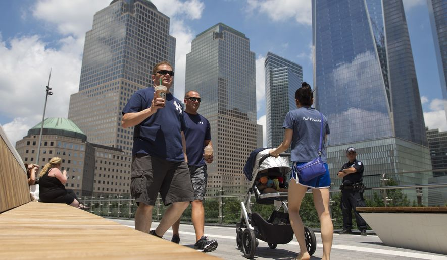 Visitors stroll through Liberty Park, Wednesday, June 29, 2016, in New York. The one-acre, elevated Liberty Park opened to the public Wednesday. Built on top of a security center, it overlooks the memorial to those who died in the Sept. 11 attacks. (AP Photo/Mary Altaffer)