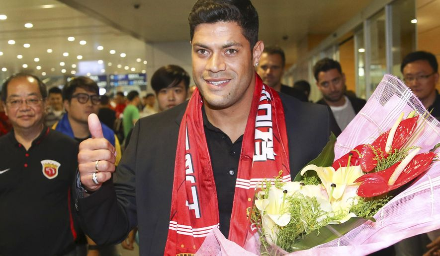 Brazilian soccer player Hulk gives a thumbs-up as he arrives to fans waiting at the airport in Shanghai Wednesday, June 29, 2016. Forward Hulk is expected to join Shanghai SIPG in a deal local media is predicting could be a record for the Chinese Super League. (Color China Photo via AP) CHINA OUT