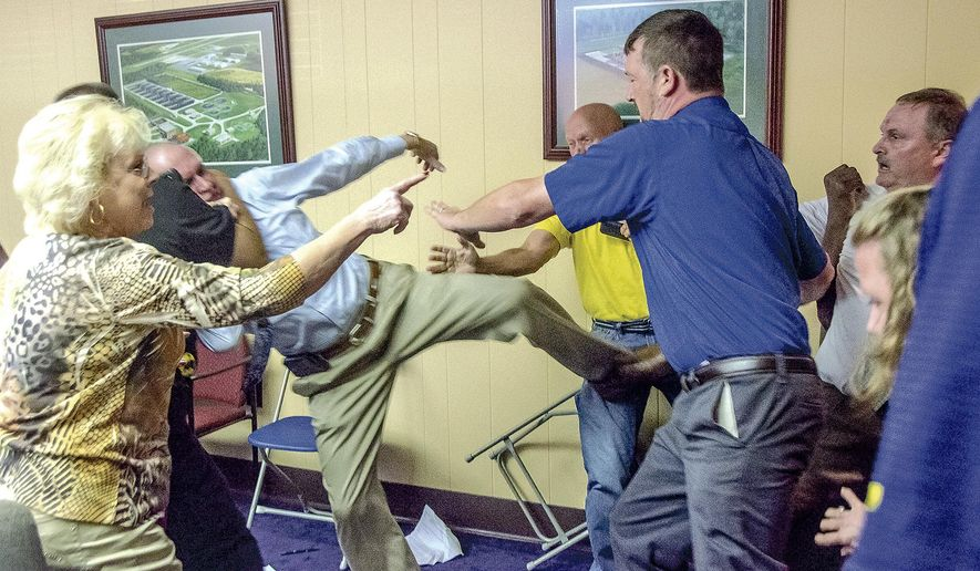 Alexander City, Ala Mayor Charles Shaw, left, is restrained by an officer after a fight broke out between him and councilman Tony Goss, far right, during a meeting of the Alexander City City Council in Alexander City, Ala. on Monday, April 25, 2016. Shaw has been found guilty of assault in an attack on a councilman during a meeting in late April. Court records filed Wednesday, June 29, 2016, say Shaw was convicted of third degree assault in Tallapoosa County District Court.  (Mitch Sneed/Alexander City Outlook via AP)