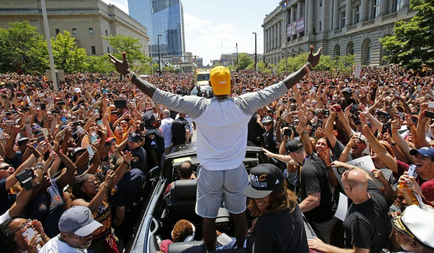 FILe - In this June 22, 2016, file photo, Cleveland Cavaliers' LeBron James, center, stands in the back of a Rolls Royce as it makes its way through the crowd lining the parade route in downtown Cleveland, celebrating the basketball team's NBA championship. Since the moment superstar LeBron James and the Cavaliers clinched the NBA championship with an historic comeback to quench the city's 52-year professional title drought, Cleveland has been celebrating like never before. (AP Photo/Gene J. Puskar, File)