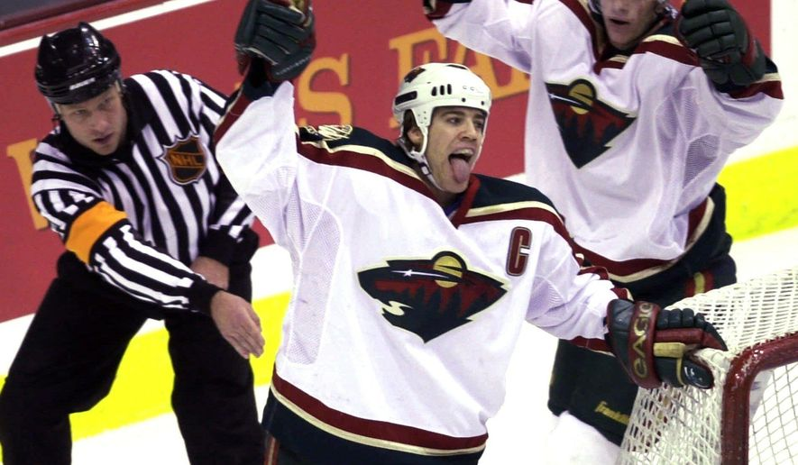 FILE - In this March 11, 2001, file photo, Minnesota Wild's Marian Gaborik, right, moves in to celebrate with teammate Darby Hendrickson, center, after Hendrickson scored a goal against the Detroit Red Wings in the first period of an NHL hockey game. Referee Brad Meier, left, signals the goal. The Wild, part of the previous wave of expansion when they entered the NHL 16 years ago, used a well-respected coach in Jacques Lemaire and a tight-knit team to reach the Western Conference finals in their third season. (AP Photo/Tom Olmscheid, File)