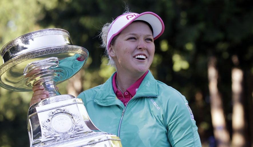 FILE- In this June 12, 2016, photo, Brooke Henderson, of Canada, holds the championship trophy after winning the Women's PGA Championship golf tournament at Sahalee Country Club in Sammamish, Wash. Henderson has come a long way since her win last year in Portland. She's ranked No. 2 in the world and has a major victory as she looks to defend her title at the Portland Classic. (AP Photo/Elaine Thompson, File)