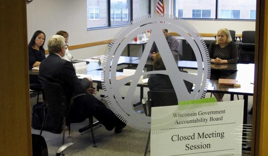 FILE - In this June 9, 2016, file photo, members of the newly created Wisconsin Ethics Commission meet in closed session with staff of the Government Accountability Board in Madison, Wis. The GAB officially disbands on Thursday, June 30, 2016, after eight years of operation. In its place will be two commissions with partisan appointees. One will oversee elections while the other handles ethics, campaign finance and lobbying laws. (AP Photo/Scott Bauer, File)