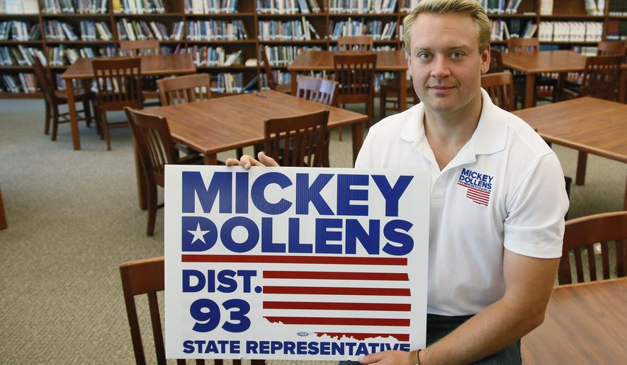 Mickey Dollens poses for a photo with one of his campaign signs in the library at U.S. Grant High School, where he used to teach English, in Oklahoma City, Wednesday, June 29, 2016. Dollens said he decided to run for the state House in Oklahoma to fix what he saw as problems the GOP-controlled Legislature was inflicting on education. Then the 28-year-old got laid off as a result of state-imposed cuts to public schools. Dollens won his Democratic primary with more than 90 percent of the vote and now advances to face a Republican in November. (AP Photo/Sue Ogrocki)