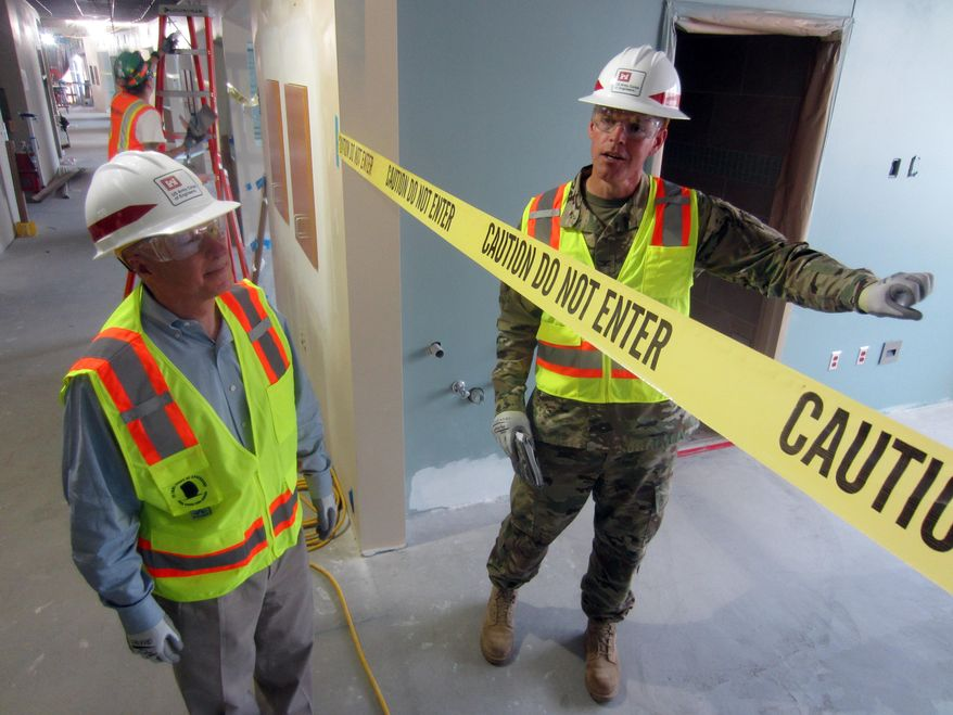 Army Corps of Engineers Col. John Henderson, right, shows Rep. Mike Coffman, R-Colo., features of a new veterans hospital under construction in Aurora, Colo., Wednesday, June 29, 2016. The Corps took over construction management from for the Veterans Affairs Department after the cost nearly tripled and legal disputes threatened to bring work to a halt. (AP Photo/Dan Elliott)