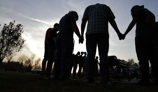 In this Sunday, April 10, 2016, file photo, youths hold hands for a prayer during a gathering at sunset outside the Christian Fellowship Church in Benton, Ky. (AP Photo/David Goldman) ** FILE **