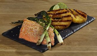 This May 23, 2016 photo shows grilled salmon, whole scallions and pineapple slices at the Institute of Culinary Education in New York. This dish is from a recipe by Elizabeth Karmel. (AP Photo/Richard Drew)